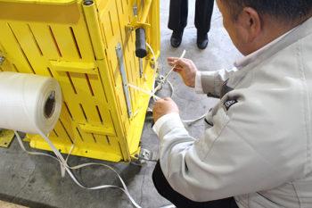 結束ひもを結び、圧縮板を上昇させます。